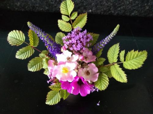 An arrangement of small flowers and foliage in an egg cup